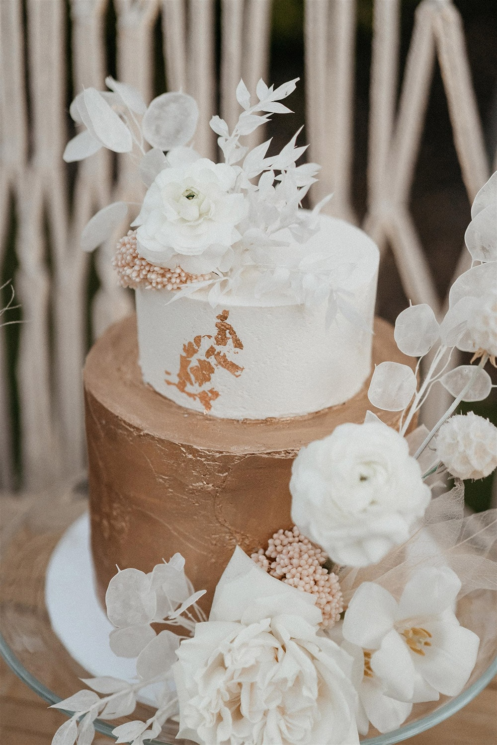 Outdoor Festival Bohemian Wedding Inspiration   A two tiered wedding cake sits on a clear glass cake plate. The top tier features smooth white buttercream with a trail of gold leaf, while the bottom tier features textured gold buttercream. The cake is decorated with artful sprays of white dried silver dollar eucalyptus, ruscus, scabiosa pods and skeleton leaves, blush dried rice flower and fresh white roses, tulips and ranunculus.   Photography: Shae Estella Photo