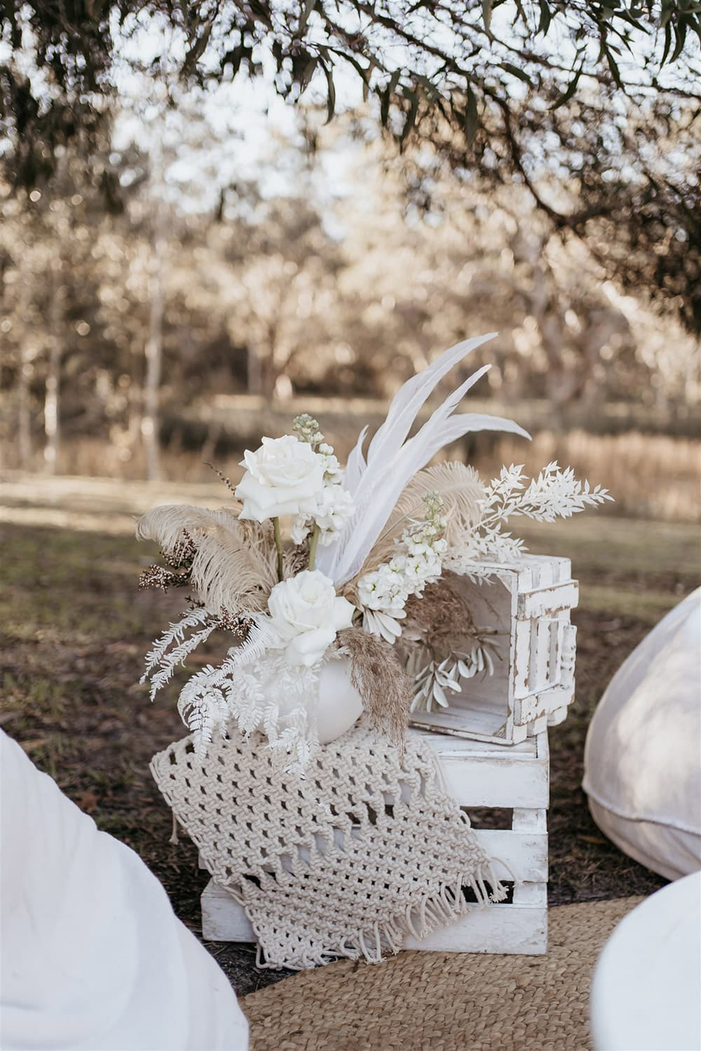 Outdoor Festival Bohemian Wedding Inspiration   Rustic white stacked crates are decorated with a macrame runner and small vase of white and neutral flowers, feathers and foliage for a boho outdoor cocktail style wedding reception.   Photography: Shae Estella Photo