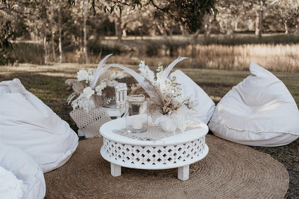 Outdoor Festival Bohemian Wedding Inspiration   The outdoor cocktail style wedding reception features a number of eclectic seating areas for guests. Here, white bean bags encircle a natural round jute rug. A small white round wooden coffee table and rustic white stacked crates complete the setting, which are decorated with macrame runners, a pillar candle in a clear glass hurricane lantern and small vases of white and neutral flowers, feathers and foliage.   Photography: Shae Estella Photo