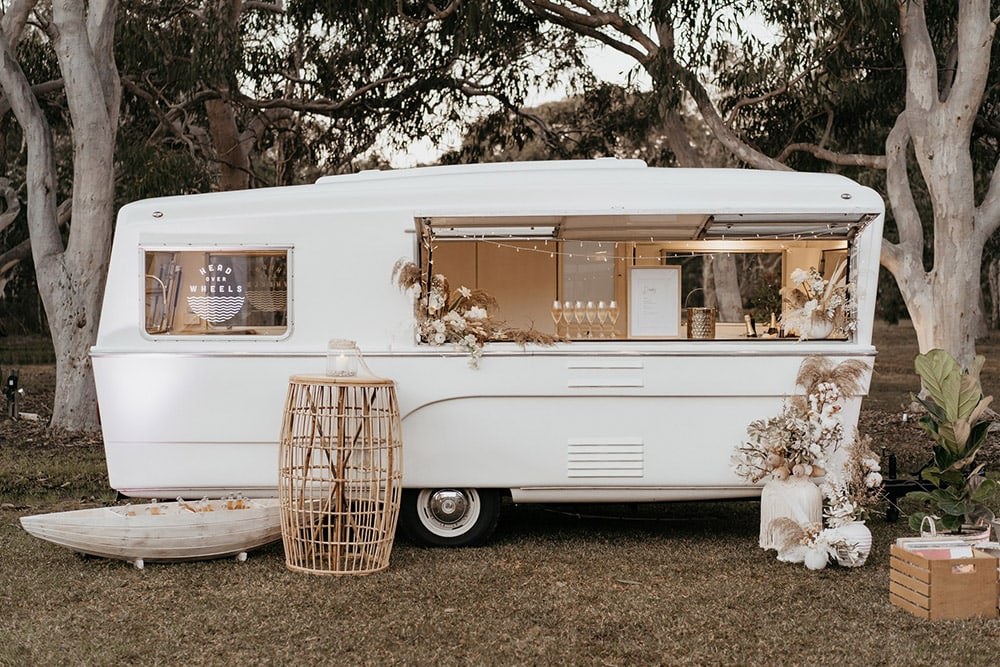 Outdoor Festival Bohemian Wedding Inspiration   After the wedding ceremony, guests are served drinks from a white vintage caravan bar and miniature row boat filled with beer on ice. This setting is styled with white and neutral floral arrangements to match the rest of the boho wedding decor.   Photography: Shae Estella Photo