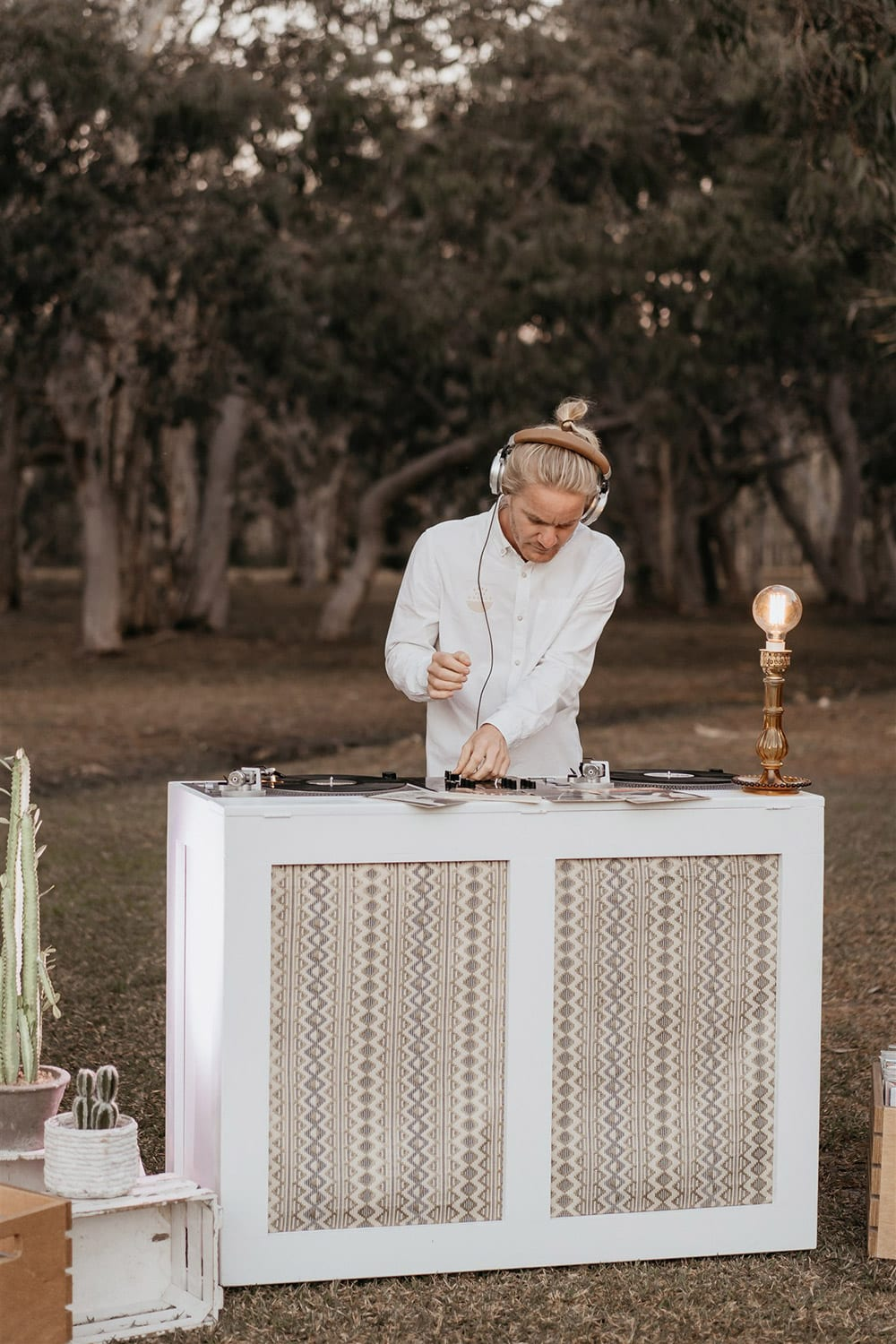 Outdoor Festival Bohemian Wedding Inspiration   A wedding DJ sets a laid-back party atmosphere with the retro sounds of vinyl records. Two neutral geometric fabric panels feature on the front of his white timber DJ station, which is topped with an amber glass table lamp with bare Edison bulb.   Photography: Shae Estella Photo
