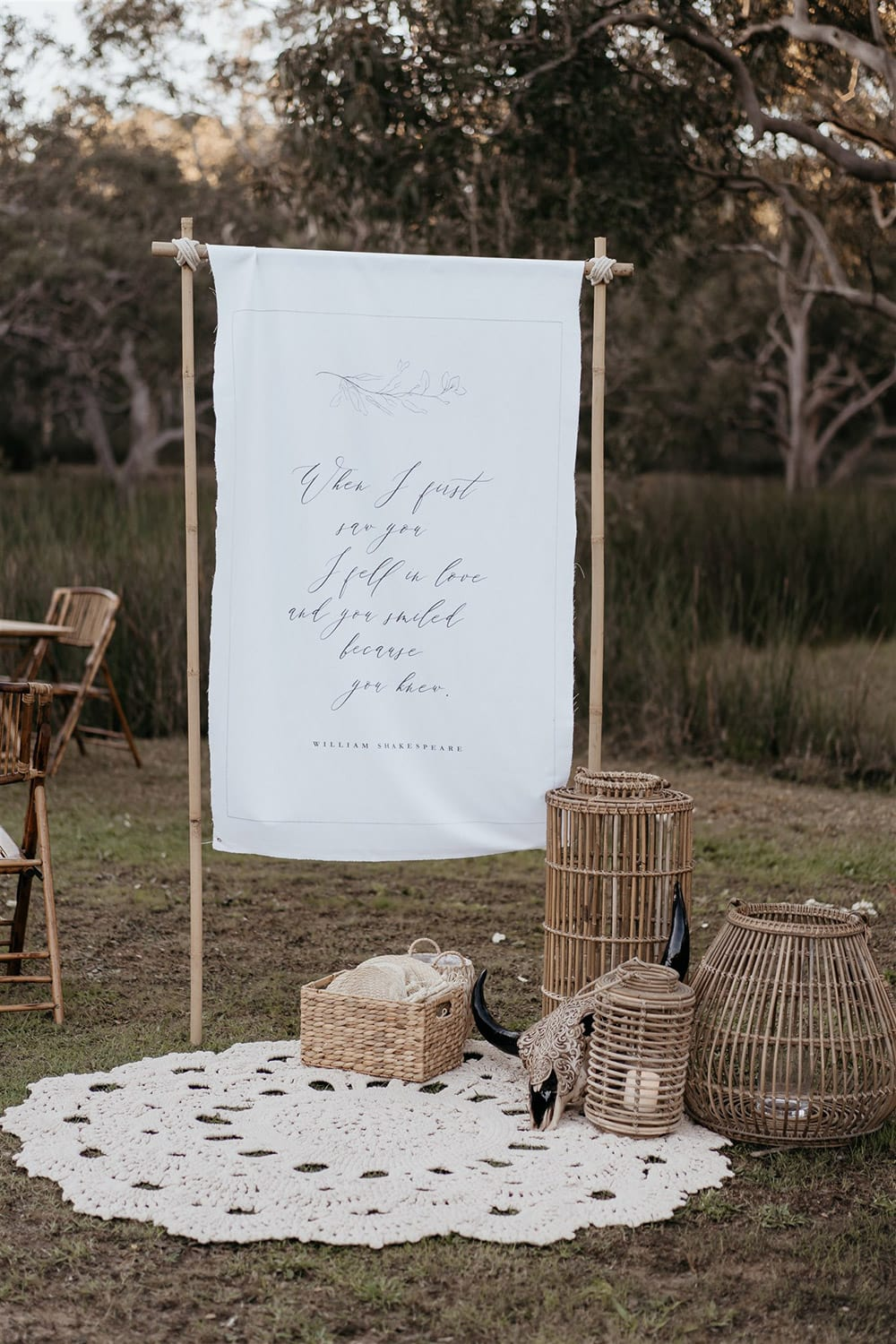 """Outdoor Festival Bohemian Wedding Inspiration   A white fabric wedding welcome sign features the same fine line foliage illustration as the stationery suite and the William Shakespeare quote, """"When I first saw you I fell in love and you smiled because you knew."""" A cluster of bamboo lanterns and a woven basket of jute fans sits atop a macrame rug alongside the welcome sign.   Photography: Shae Estella Photo"""