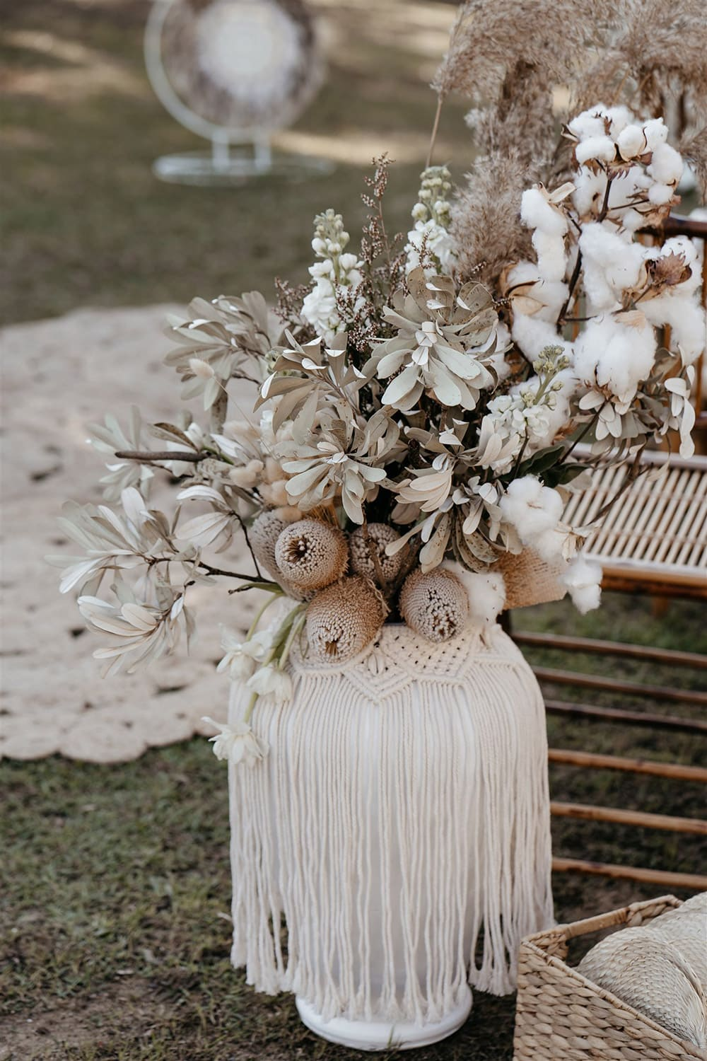Outdoor Festival Bohemian Wedding Inspiration   This outdoor boho wedding ceremony consists of woven jute rugs for the aisle and two pillars of white circles in varying sizes adorned with macrame, feathers and flowers for the arbour. The setting is framed by bamboo folding chairs for guests and large white vases decorated with fringed macrame wraps that are filled with neutral dried floral arrangements accented with stems of white tulips, stocks, cotton and ruscus.   Photography: Shae Estella Photo