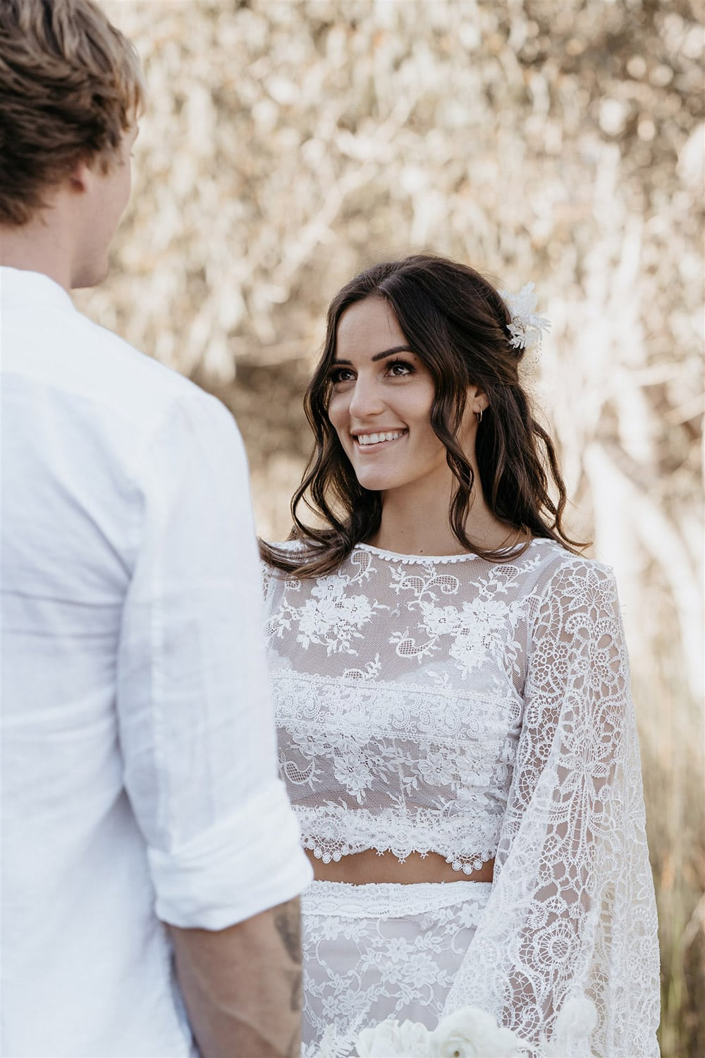 Outdoor Festival Bohemian Wedding Inspiration   The bride wears a white two piece lace boho wedding dress with a long sleeved cropped bodice and tiered maxi skirt. Her hair is worn in a romantic half up half down style with loose waves and a cascading fresh floral hairpiece.   Photography: Shae Estella Photo