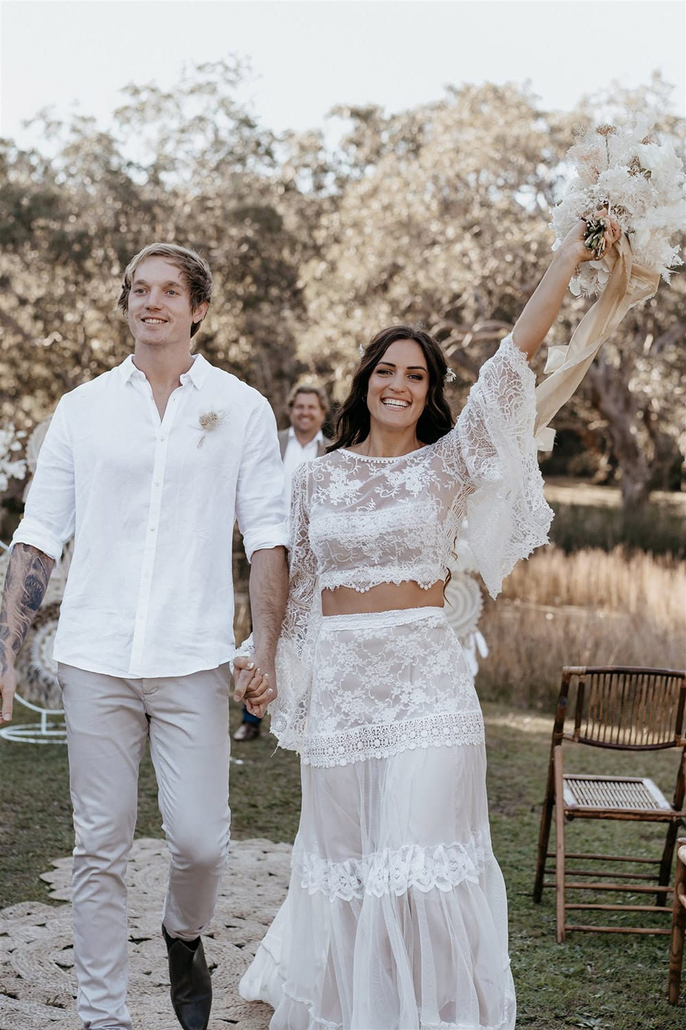 Outdoor Festival Bohemian Wedding Inspiration   The bride wears a white two piece lace boho wedding dress with a long sleeved cropped bodice and tiered maxi skirt. Her hair is worn in a romantic half up half down style with loose waves and a cascading fresh floral hairpiece. The groom wears an untucked white linen shirt with the sleeves rolled up and collar unbuttoned, light grey chinos and brown boots for a casual wedding day look.   Photography: Shae Estella Photo