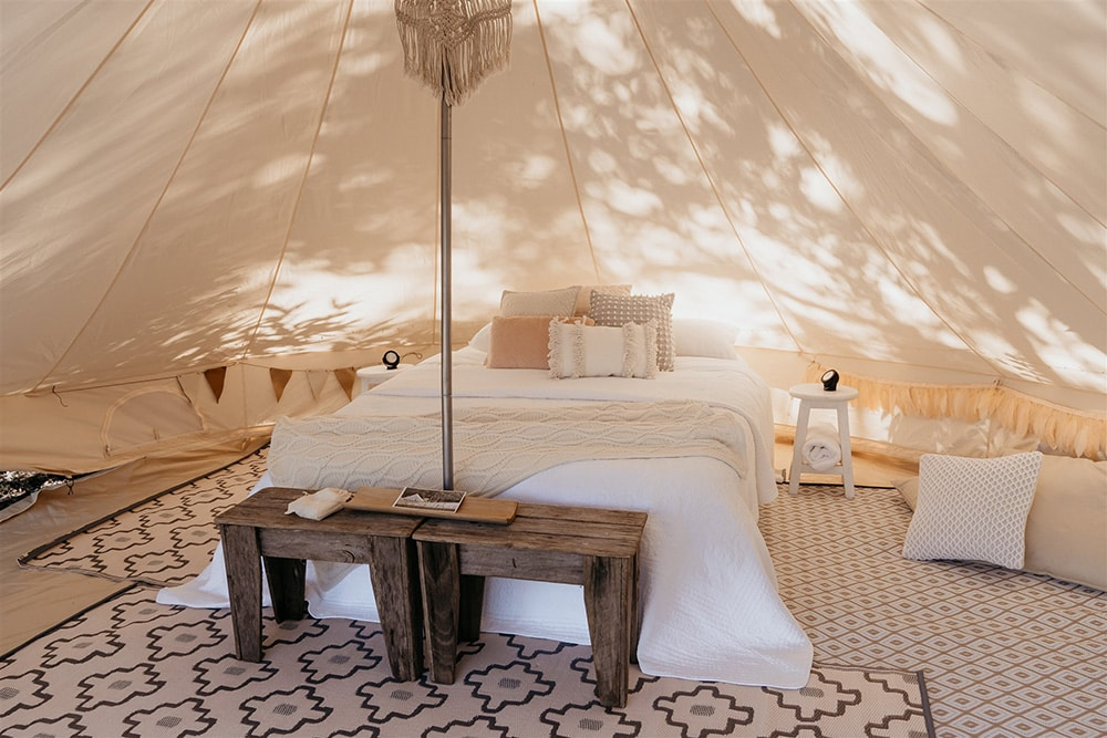Outdoor Festival Bohemian Wedding Inspiration   A bronze, neutral and white balloon installation frames the entrance to the couple's glamping tent, styled with layered bohemian rugs, throw pillows, a queen bed, camp chairs, fabric garlands, wooden furnishings and wicker decor.   Photography: Shae Estella Photo