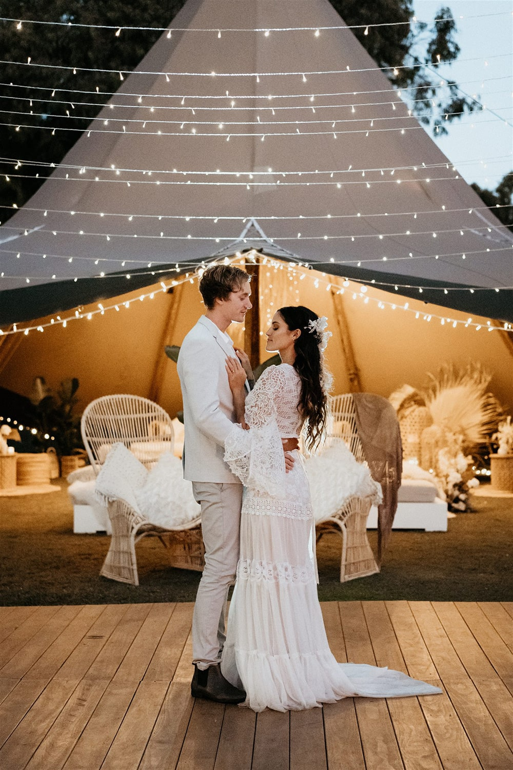 Outdoor Festival Bohemian Wedding Inspiration   This loved-up couple shares their first dance on a timber dance floor beneath a canopy of twinkling fairy lights and in front of a large tipi styled with eclectic lounge seating.   Photography: Shae Estella Photo