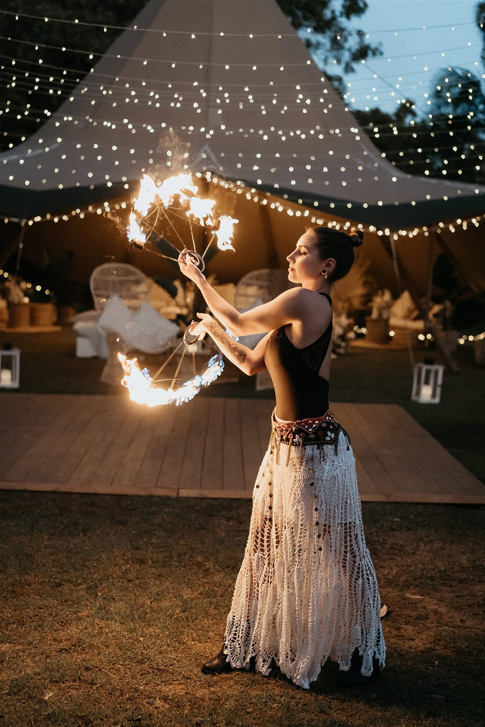 Outdoor Festival Bohemian Wedding Inspiration   A fire twirler performs as wedding entertainment in front of a canopy of fairy lights and large tipi styled with eclectic lounge seating for an outdoor boho wedding reception.   Photography: Shae Estella Photo