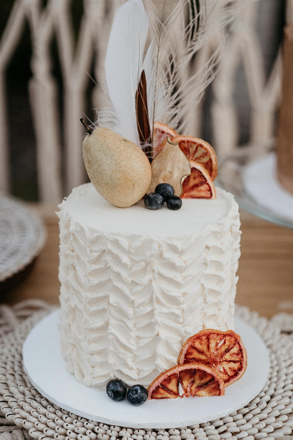 Outdoor Festival Bohemian Wedding Inspiration   A second single tier white buttercream wedding cake features bold chevron texture, dried orange slices, whole pear, blueberries and assorted feathers.   Photography: Shae Estella Photo
