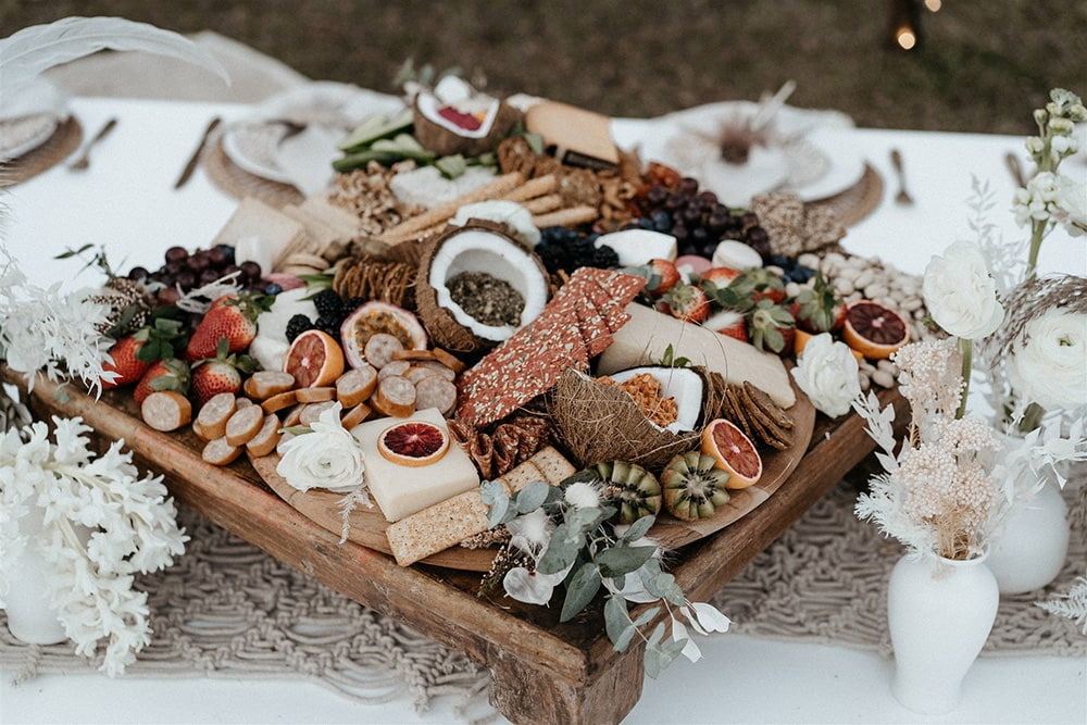 Outdoor Festival Bohemian Wedding Inspiration   A white timber picnic table is topped with a macrame runner, clusters of white vessels displaying fresh posies and a generous antipasto grazing platter ready for the happy couple and their crew!   Photography: Shae Estella Photo