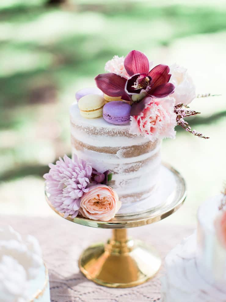 Naked wedding cake with macarons and pastel flowers