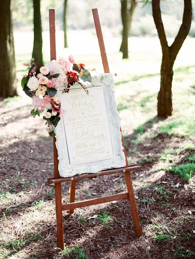 Gold wedding sign in ornate frame with florals