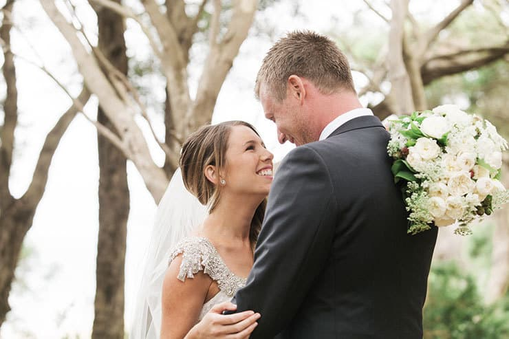 Bride smiling at groom holding flowers