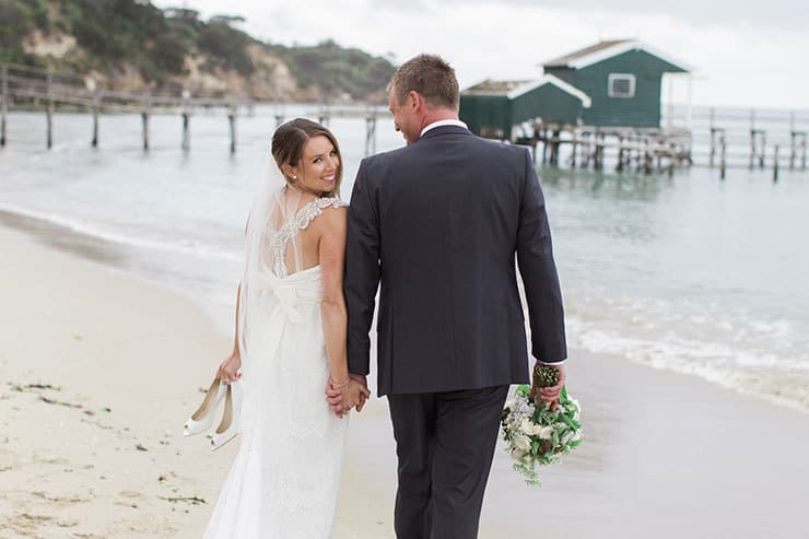 Bride looking over shoulder on the beach carrying wedding shoes with groom