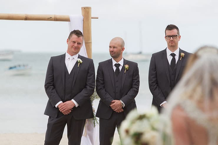 Groom and groomsmen waiting for bride at end of aisle