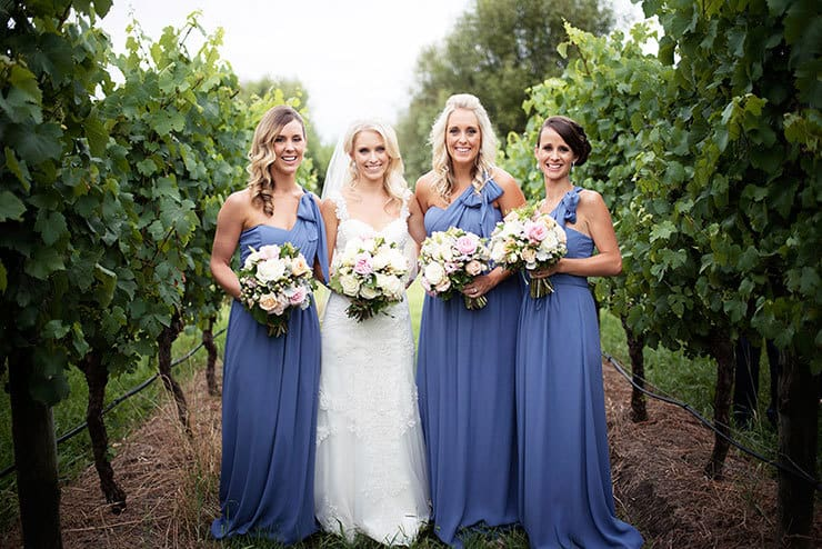 Bride with bridesmaids in blue dresses with pink and white bouquets