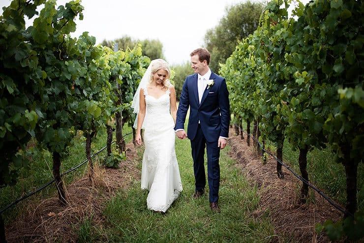 Elegant bride and groom walking through vineyards