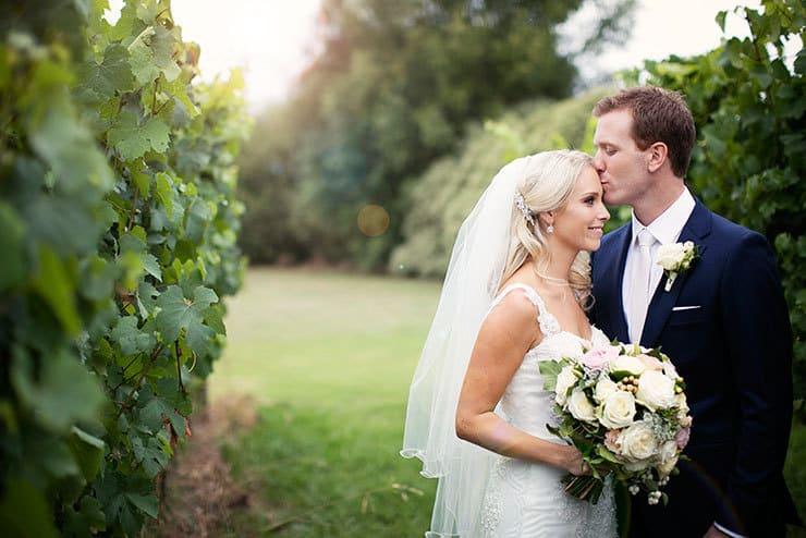 Pretty winery wedding bride and groom forehead kiss