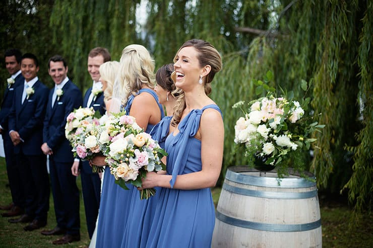 Bridesmaids in blue dresses with pink and white bouquets at ceremony