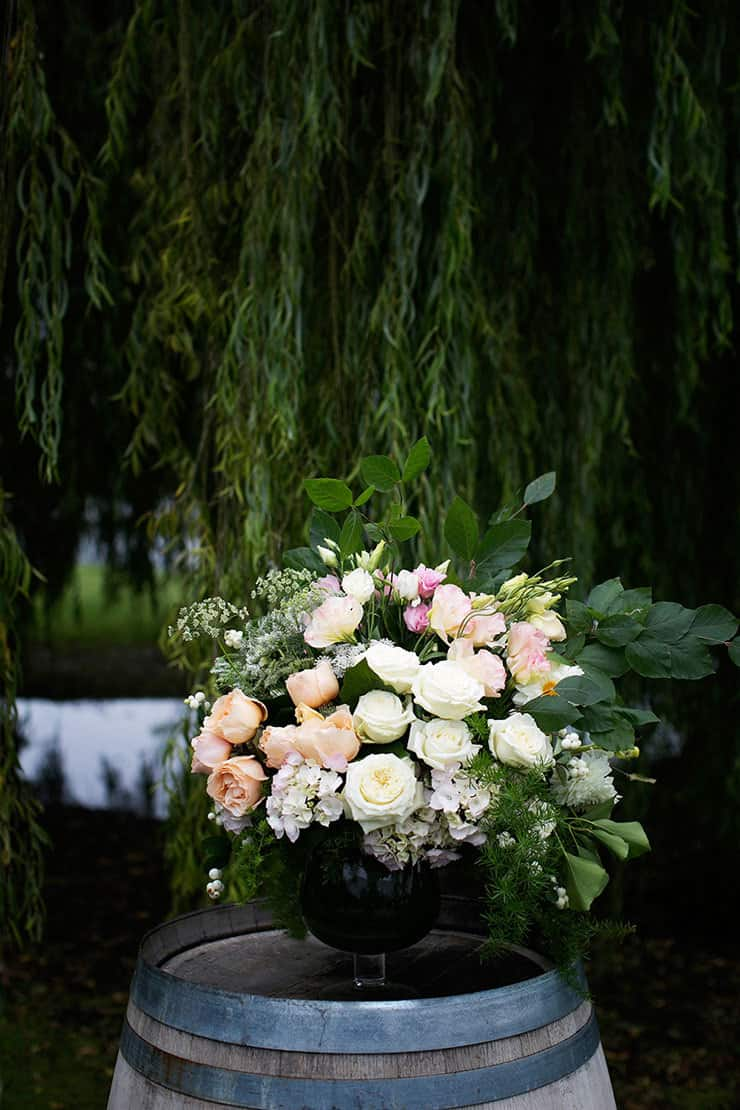 Wine barrel ceremony aisle decor with large pink and white flower arrangement