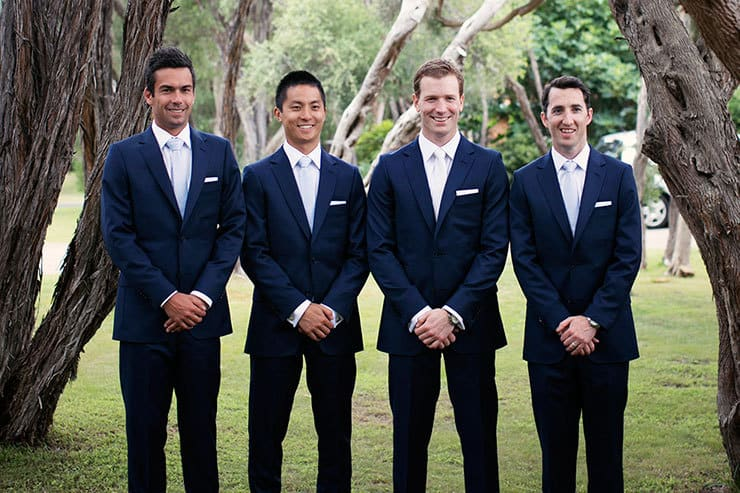 Groom and groomsmen in navy suits with light blue and white ties