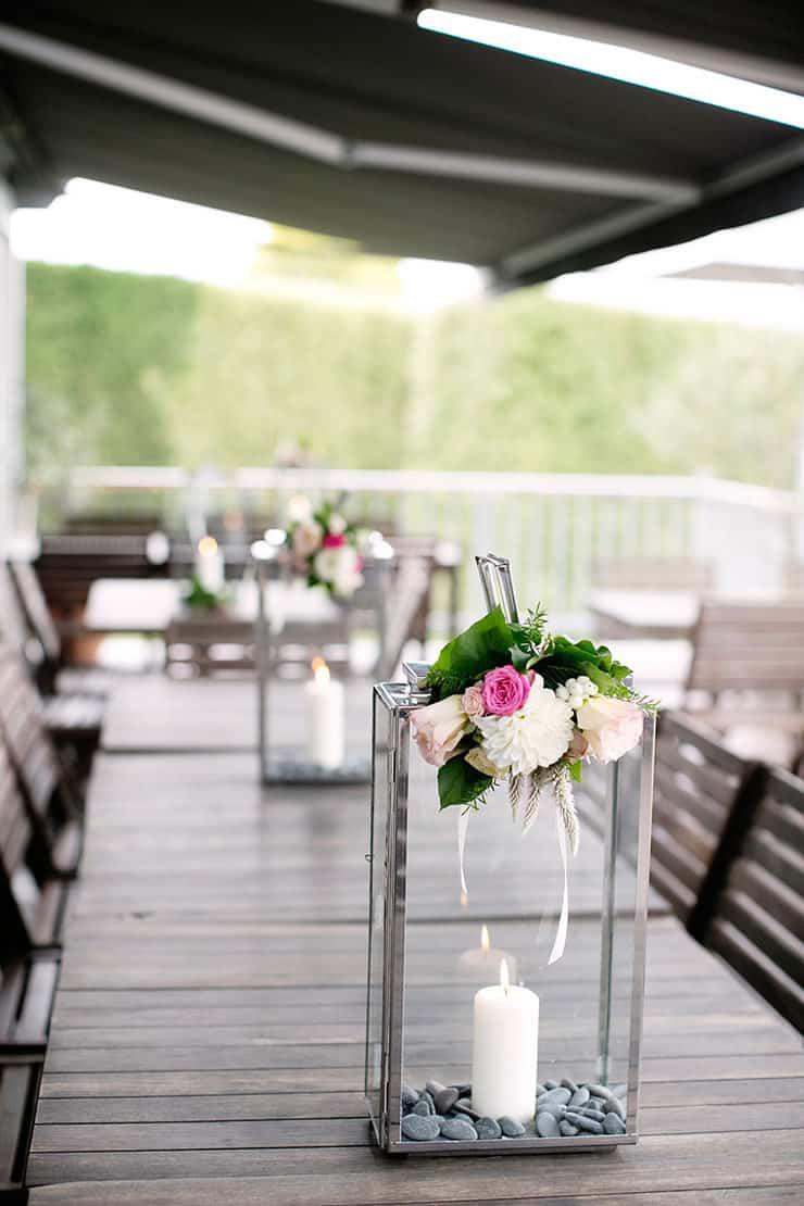 Pretty winery wedding reception lantern centrepieces with flowers