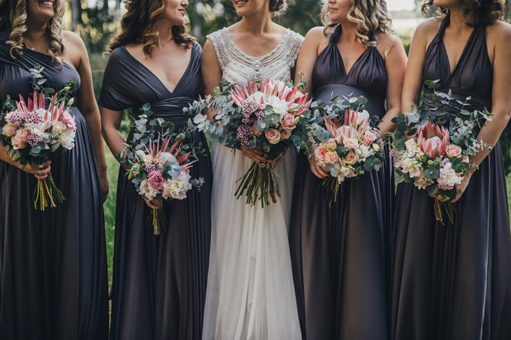 Purple grey bridesmaid dresses with Protea wedding bouquets