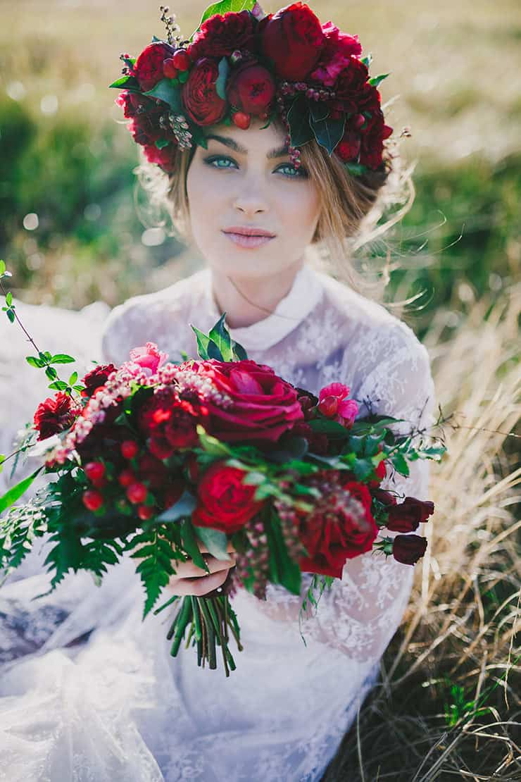 Bohemian bride wearing natural makeup with relaxed updo and red flower crown