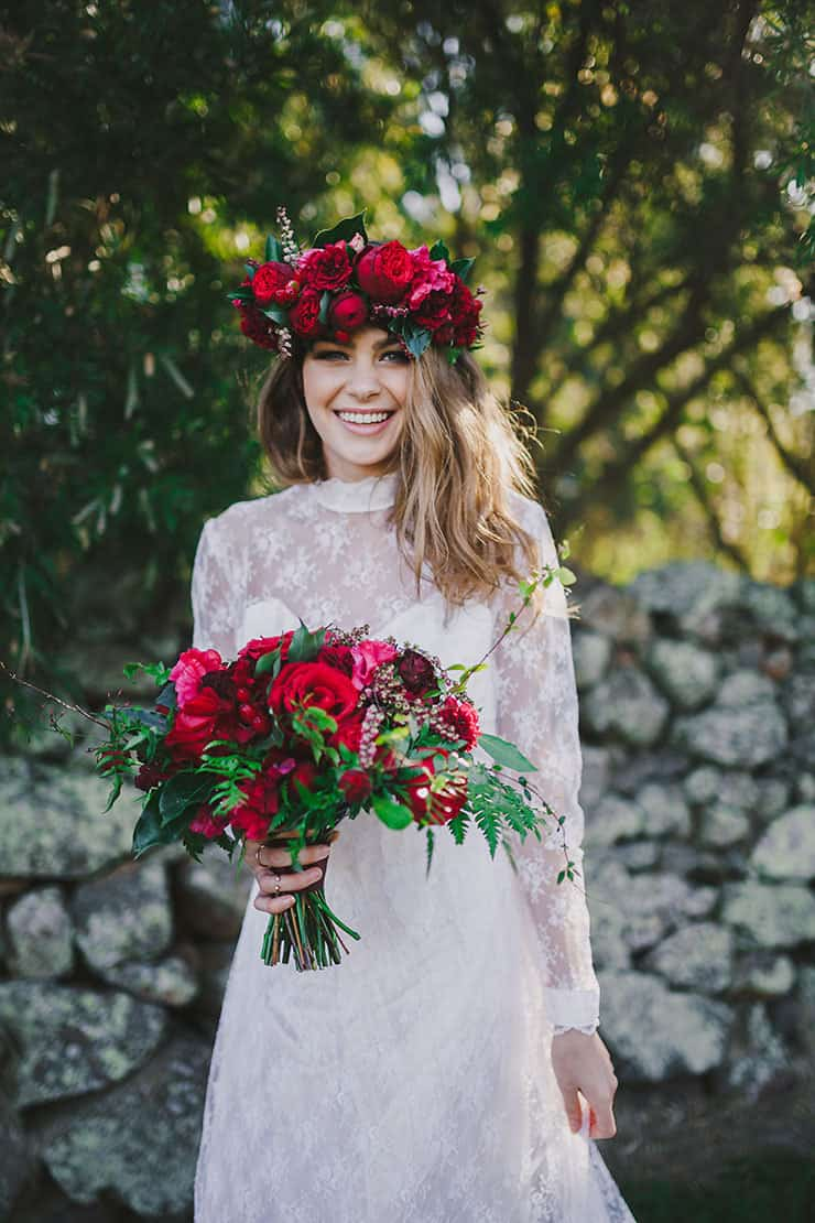 Relaxed bride wearing red flower crown with holding wedding bouquet