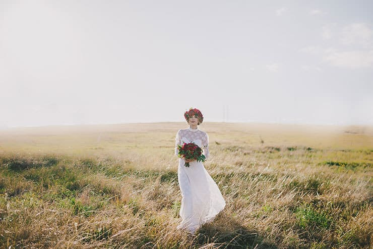 Bohemian bride wearing vintage lace wedding dress with red flower bouquet and crown