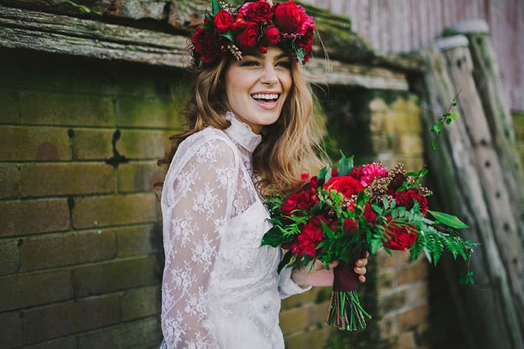 Relaxed bride wearing red flower crown and holding bouquet