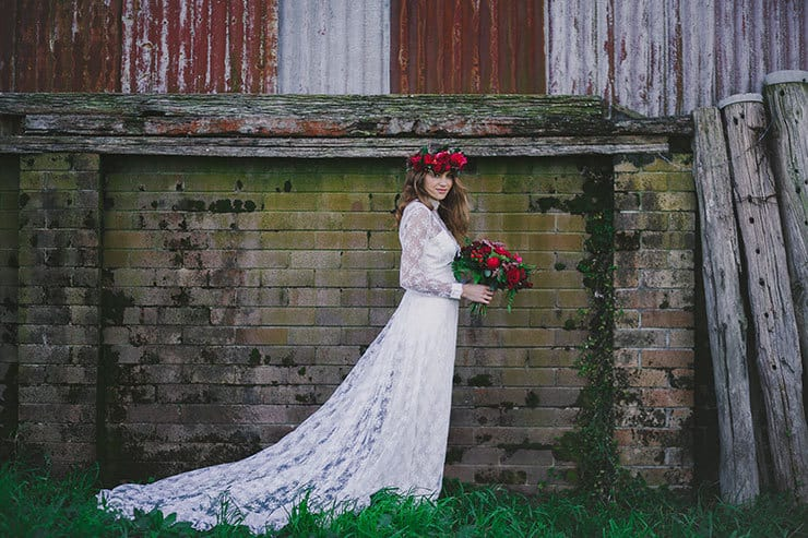 Boho bride wearing vintage lace wedding dress and red flower crown