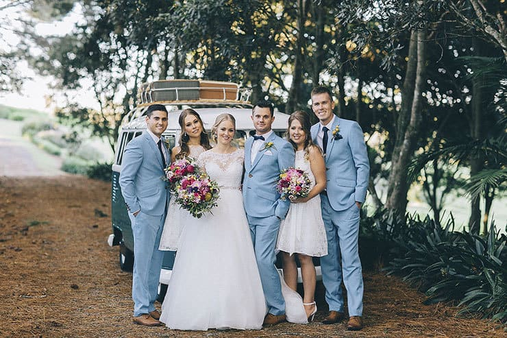 Bridal party wearing white bridesmaid dresses and light blue suits