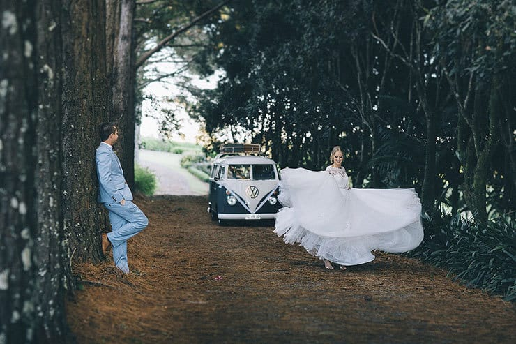 Bride twirling wedding dress as groom looks on