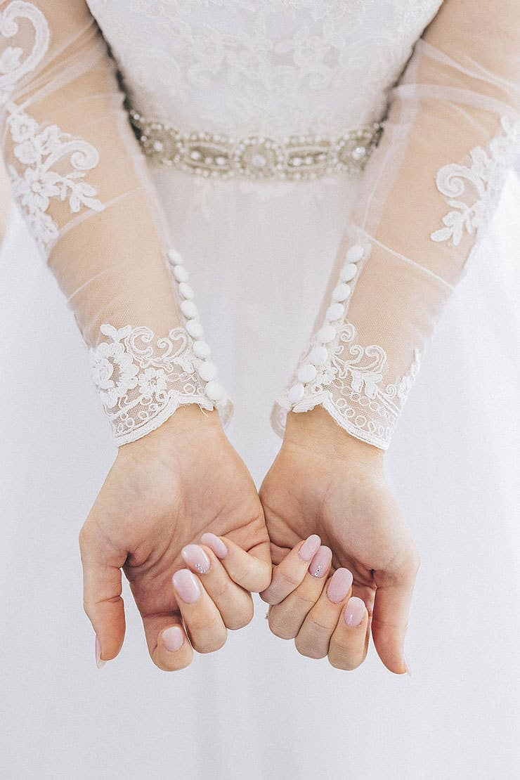 Wedding day manicure and detailed dress sleeves