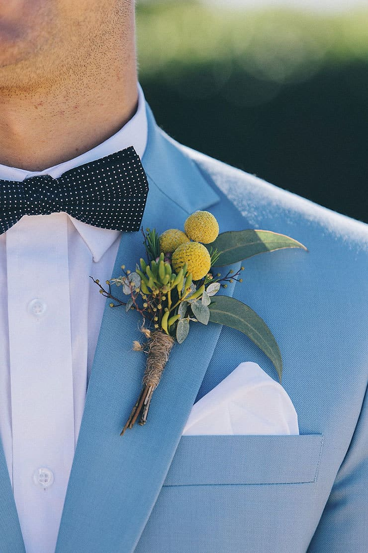 Light blue suit with polka dot bow tie and rustic yellow buttonhole