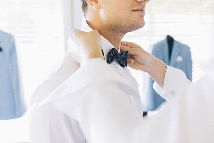 Groom getting ready with polka dot bow tie