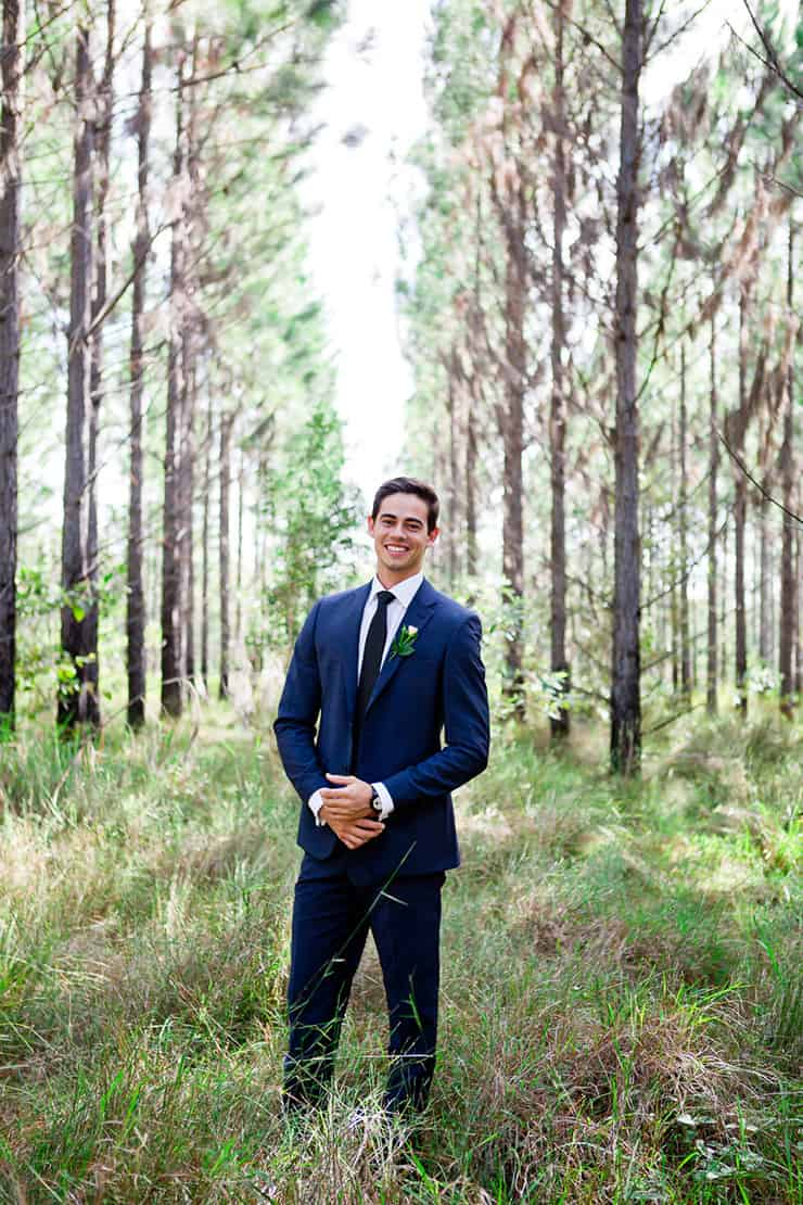 Groom wearing navy suit and dark blue tie