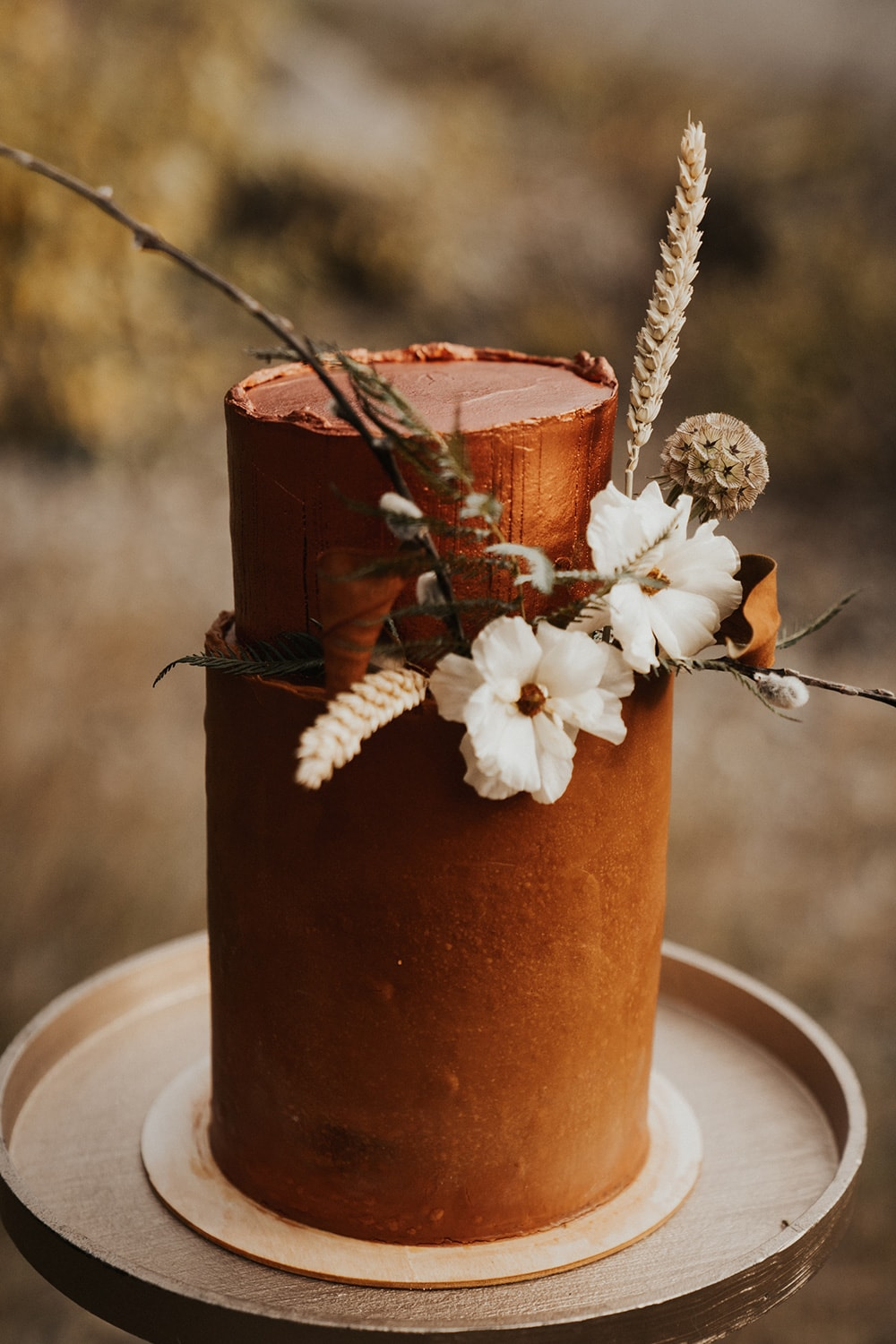 Boho Rust & White Wedding Ideas |  Tall rust coloured two tiered buttercream wedding cake with a small arrangement of rustic white and dried flowers between the first and second tier. | Photography: Anna Tee Photography via Storyboard Wedding