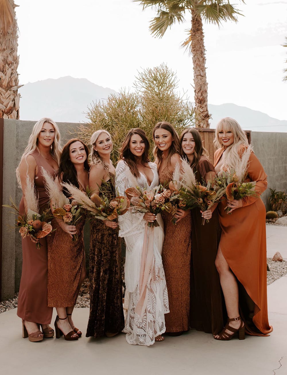Boho Rust & White Wedding Ideas | Boho bridesmaids wearing mismatched dresses in earthy colours like burnt orange, terracotta and rust. The bride stands in the centre of the group wearing a white boho wedding dress featuring long bell sleeves, a plunging V neckline and lace in a bold foliage pattern. The wedding party wear their hair down in relaxed waves and carry neutral boho wedding bouquets featuring pampas grass, protea, anthurium and roses. The bride's bouquet is tied with long flowing blush ribbons. | Photography: Ashley M. Clayton via Green Wedding Shoes
