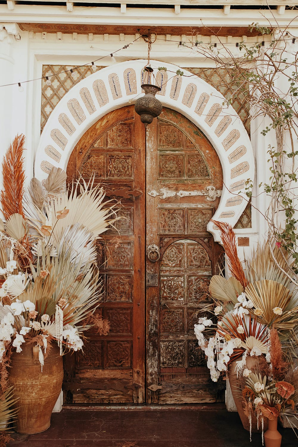 Boho Rust & White Wedding Ideas | An ornately carved wooden door inspired by Moroccan architecture used as a boho wedding ceremony backdrop. It is framed by large ceramic pots filled with wild floral arrangements consisting of dried palm leaves and anthurium in earthy colours, white orchids, amaranthus and roses. | Photography: Jordan Voth via Foxtail Florals