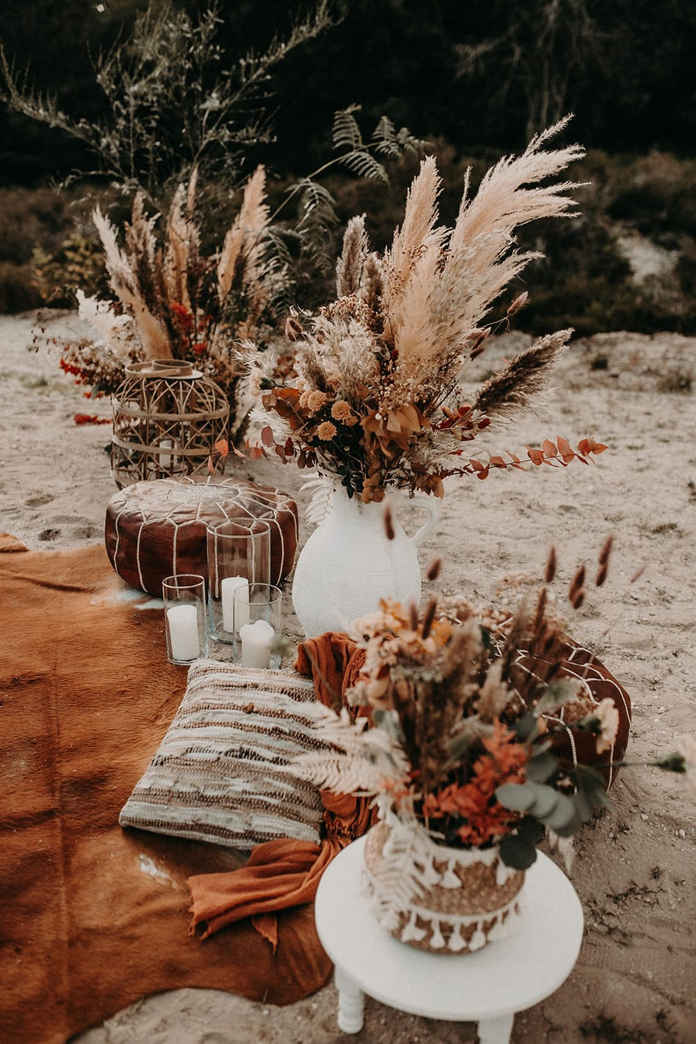 Boho Rust & White Wedding Ideas | Create a relaxed outdoor wedding seating area with a rust coloured rug, scattered floor cushions, white pillar candles in glass hurricane vases, large bamboo lantern, white low set table and earthy dried flower arrangements in eclectic vessels featuring wild pampas grass. | Photography: Mel Ende Photography