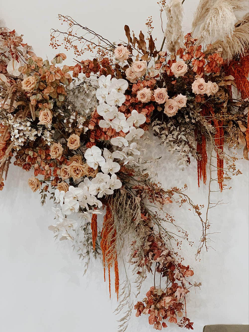 Boho Rust & White Wedding Ideas | An earthy boho wedding ceremony backdrop consisting of a floating asymmetrical floral arrangement hung on a white wall which features blush roses, white orchids, rust coloured bougainvillea and dripping amaranthus, and neutral feathery foliage. | Photography & Flowers: Nikau Flora