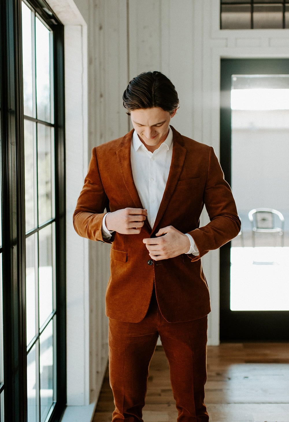 Boho Rust & White Wedding Ideas | Groom wearing a rust coloured wedding suit with a white shirt and no tie. | Photography: Peyton Rainey Photography