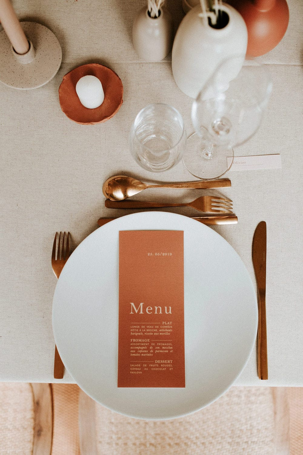 Boho Rust & White Wedding Ideas | A minimalist wedding reception place setting features an oatmeal linen tablecloth, round white plate topped with rectangular rust coloured menu printed with white text, gold cutlery, a terracotta candle plate and small ceramic vases in earthy colours filled with dried flowers. | Photography: Pinewood Weddings via La mariée aux pieds nus