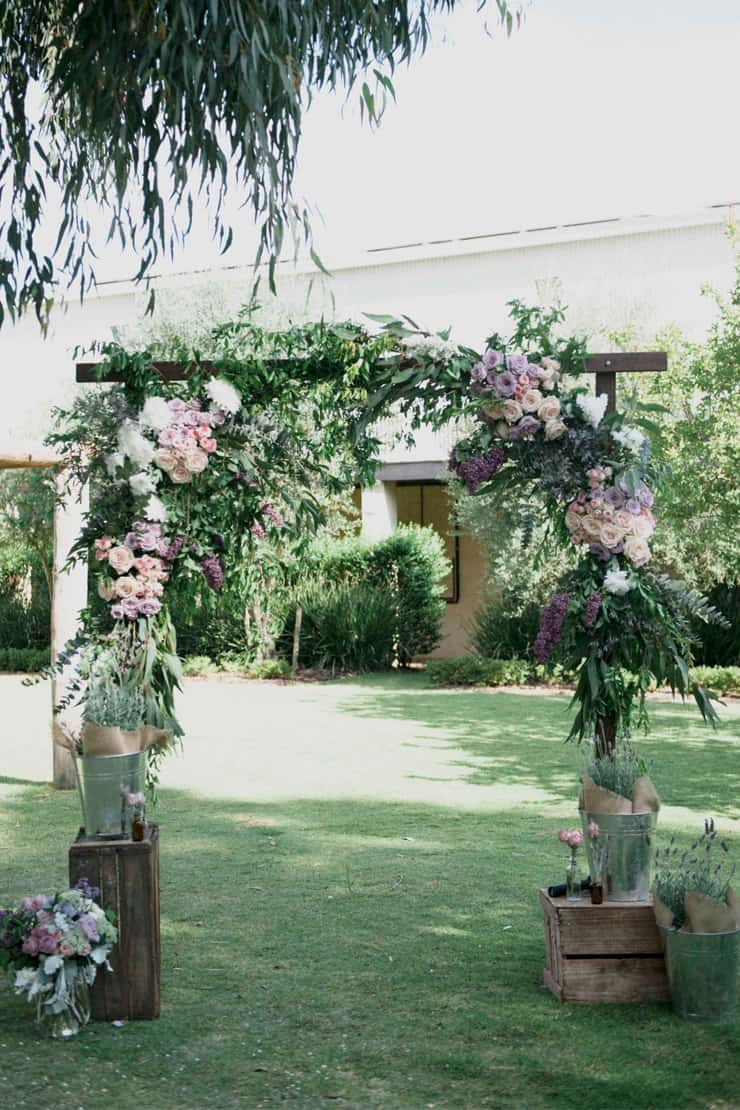 Rustic wedding ceremony arbour filled with purple and pink flowers