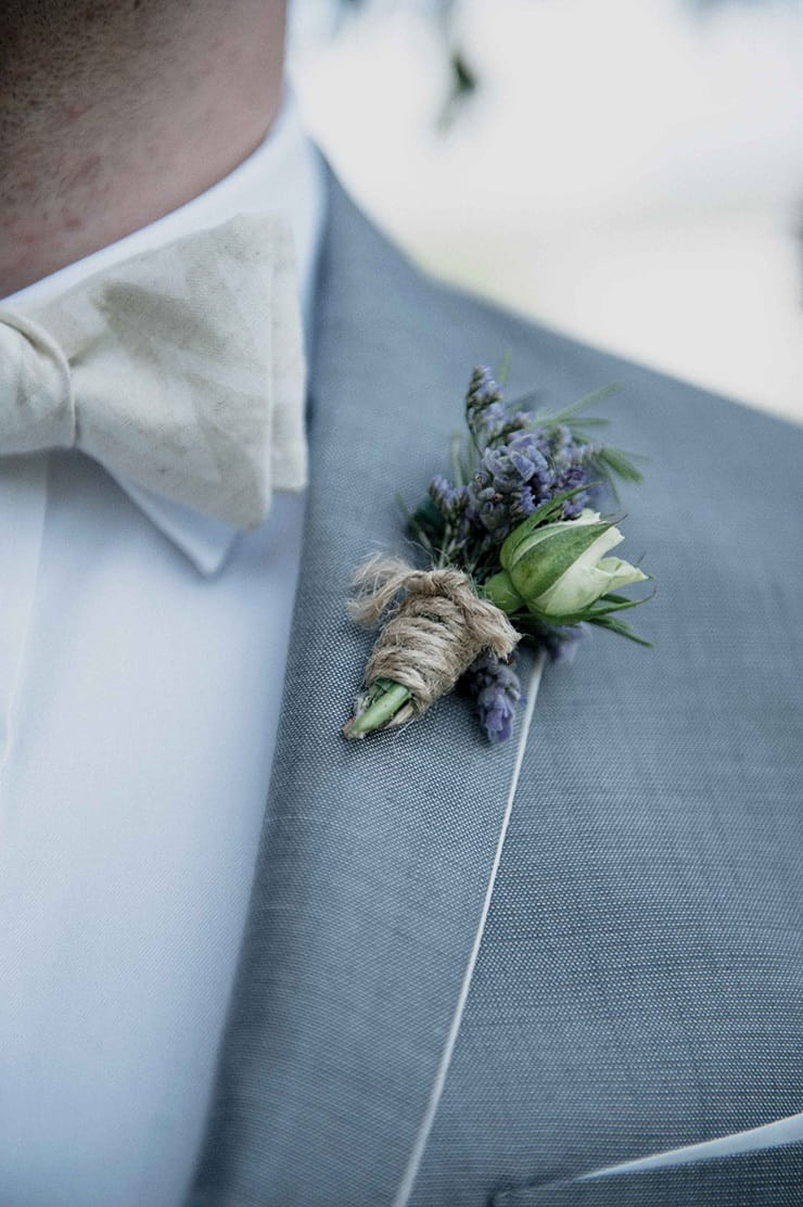 Groom wearing grey suit with a rustic lavender and rose boutonniere