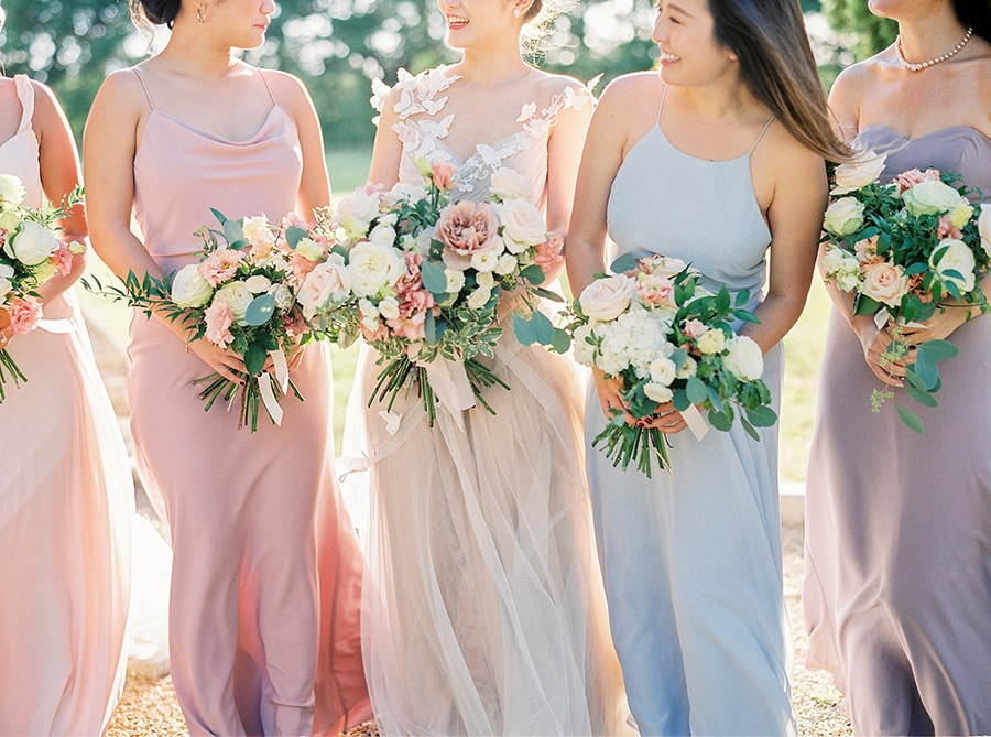 Romantic spring pastel bridesmaid dresses in pale blue, blush pink and purple paired with soft pink and white bouquets | Photography: Branco Prata via Martha Stewart Weddings