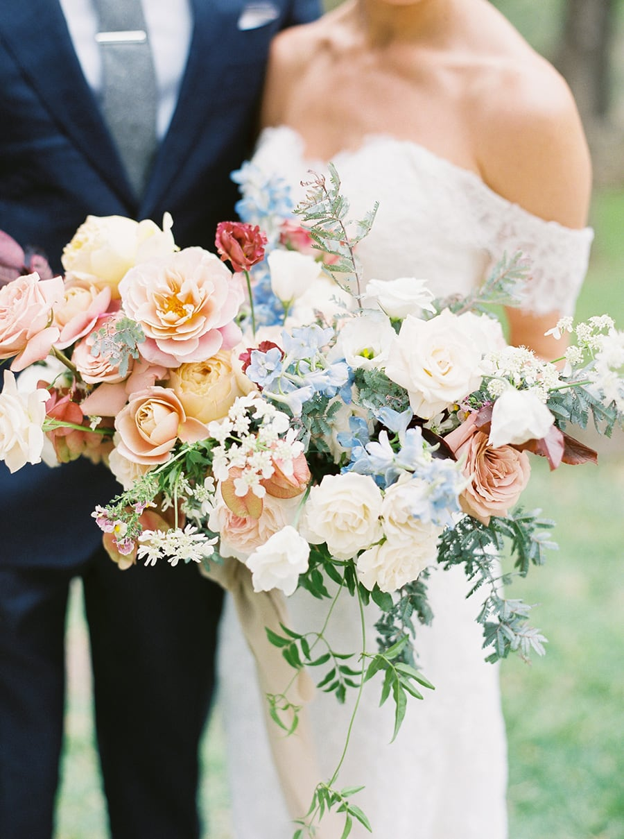 Romantic spring pastel wedding bouquet in pale blue, blush pink, butter yellow and white featuring roses, delphinium, and greenery | Photography: Brittany Jean Photography