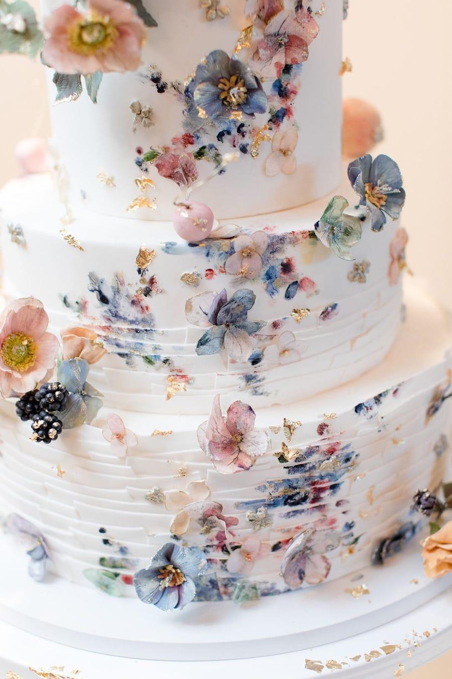 Spring pastel painted fondant wedding cake with delicate sugar flowers and gold leaf | Photography: Jaye Kogut